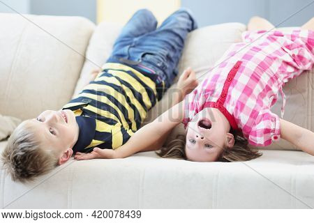 Little Boy And Girl Lying On Couch Upside Down At Home