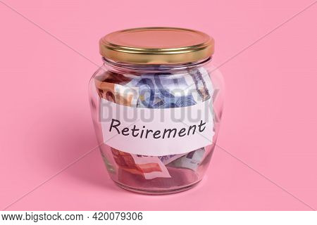 Money Box With Word Retirement On Sticky Note Paper. Euro Banknotes In Glass Money Jar With Savings