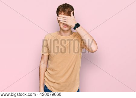 Young caucasian man wearing casual clothes covering eyes with hand, looking serious and sad. sightless, hiding and rejection concept