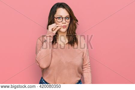 Young plus size woman wearing casual clothes and glasses mouth and lips shut as zip with fingers. secret and silent, taboo talking
