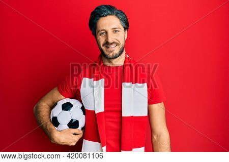 Young hispanic man football hooligan holding ball looking positive and happy standing and smiling with a confident smile showing teeth