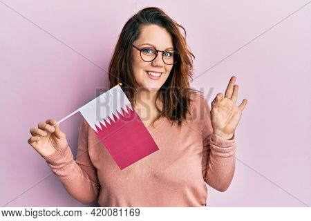 Young caucasian woman holding qatar flag doing ok sign with fingers, smiling friendly gesturing excellent symbol