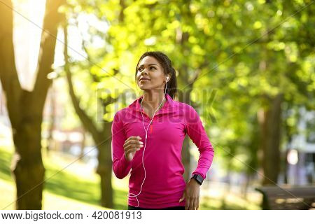 African Woman Jogger Training At Public Park