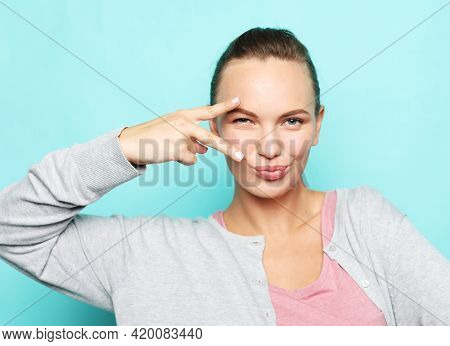 Lifestyle, emotion and young people concept: Give peace a chance. Portrait of a pretty young woman showing the peace sign on blue background.