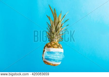 Pineapple In Medical Mask On Color Blue Background. Pineapple Fruit In Face Mask In Covid Lockdown.
