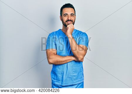 Handsome hispanic man with beard wearing blue male nurse uniform looking confident at the camera with smile with crossed arms and hand raised on chin. thinking positive.