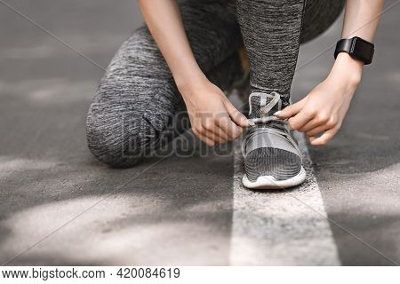 Closeup Of Sporty Female Tying Shoes Before Running Outdoors, Cropped Image