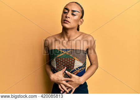 Hispanic man wearing make up and long hair wearing womans top with hand on stomach because indigestion, painful illness feeling unwell. ache concept.