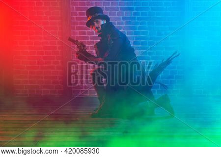 Full length portrait of a courageous steampunk male warrior posing with a gun on a brickwall smoky background. World of steampunk.