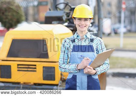 Woman Builder In Protective Helmet Holding Clipboard With Documents In Hands On Background Of Asphal