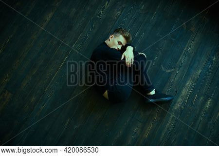Portrait of a young man in black clothes lying curl up on a floor. Feelings, emotions.