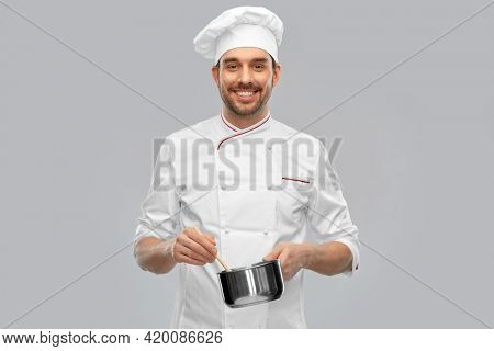 cooking, culinary and people concept - happy smiling male chef in toque with pot or saucepan over grey background