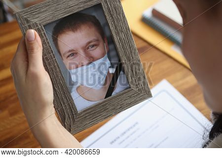 Woman Holding Portrait Of Deceased Husband With Improperly Wearing Protective Medical Mask Closeup