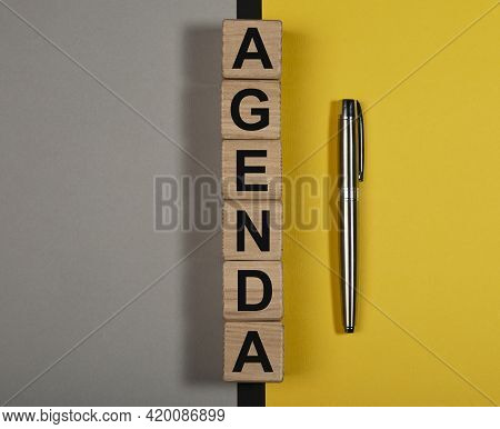 Agenda Word On Wooden Cubes On Yellow And Gray Background
