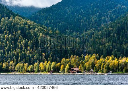A House In The Forest On The Shore Of The Lake. Beautiful Mountain Landscape, Forest Housing