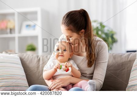 family, motherhood and people concept - happy smiling mother kissing little baby playing with teething toy or rattle at home