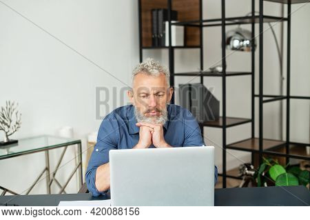 Contemporary Senior Grey Hair Businessman Sits In Front Of The Laptop Contemplating And Researching