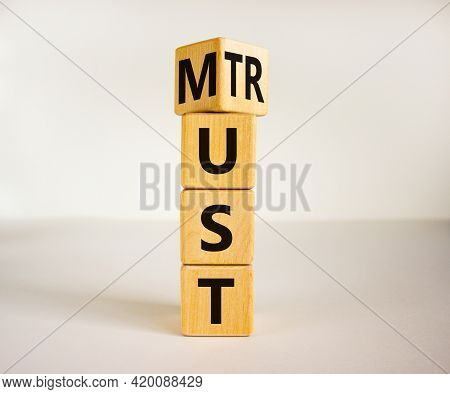 Must Trust Symbol. Turned Wooden Cubes With Words 'must Trust'. Beautiful White Table, White Backgro