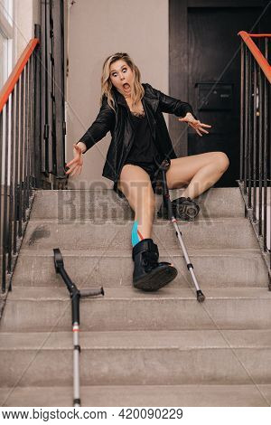 Young Woman Fell On Stairs. Broken Leg In An Orthosis And Crutches. Disabled Person . Life Insurance