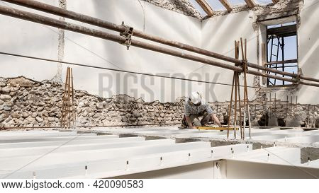 Man At Work, Construction Worker Wears Helmet And Uses The Spirit Level, Check The Beams At The Base
