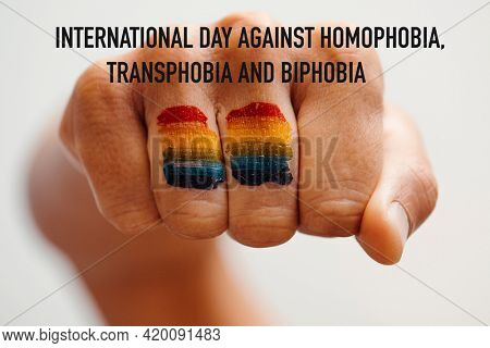 the rainbow flag painted in the fist of a young person and the text international day against homophobia, transphobia and biphobia
