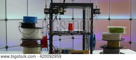 3d printer and plastic filament on color background