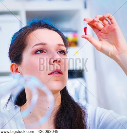Female laboratory assistant analyzing a blood sample. Tect tube with biological sample