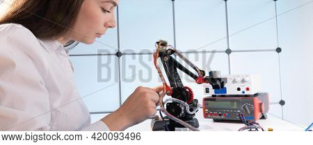 A young woman writes an algorithm for the robot arm. Science Research Laboratory for Robotic Arm Model. Computer Laboratory