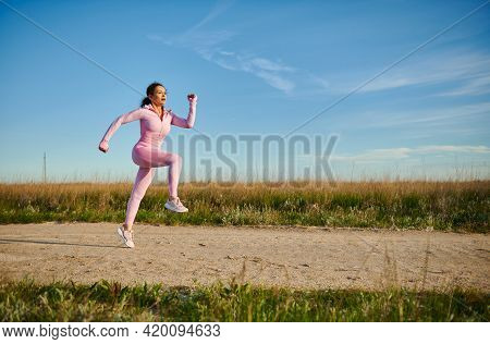 Young Sporty Woman In Pink Sportswear Jogging Outdoors On A Beautiful Sunny Early Summer Day. Sport.