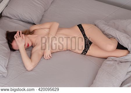 Sexy Attractive Seductive Woman In Black Lace Panties On Bed With Grey Sheets. Erotic Ladies Concept
