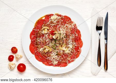 Beef Carpaccio Is Beautifully Served On A White Plate And Garnished With Tomatoes, Champignons And C