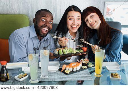 Three Joyful Multiracial Friends, Eating Sushi Rolls, Using Bamboo Sticks. Young Diverse People Enjo