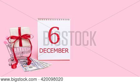 6th Day Of December. A Gift Box In A Shopping Trolley, Dollars And A Calendar With The Date Of 6 Dec