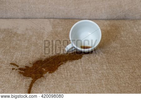 Spilled Cup Of Coffee On The Sofa With Dirty Stain.