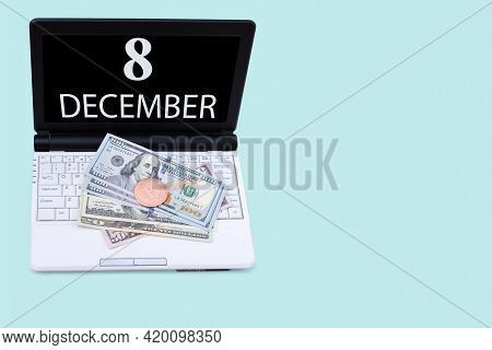 8th Day Of December. Laptop With The Date Of 8 December And Cryptocurrency Bitcoin, Dollars On A Blu