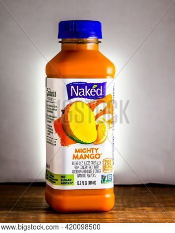Bottle with Mighty Mango drink from Naked on wooden table