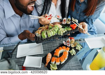 Multiracial Friends Eating Sushi At Cafe. Tasty Sushi Rolls Maki Served On Plate. Close Up Shot Of S