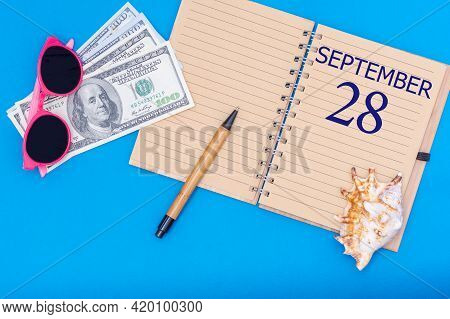 28th Day Of September. Travel Concept Flat Lay - Notepad With The Date Of 28 September Pen, Glasses,