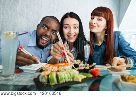 People, Food And Friendship Concept. Three Happy Young Friends Enjoying Sushi At A Japanese Restaura