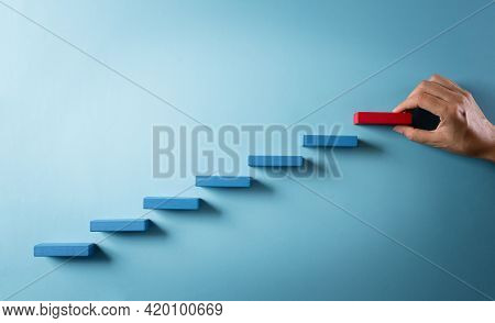 Concept Of Building Success Foundation. Hand Holding Wooden Block Stacking As Step Stair, Success In