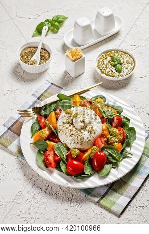 Spinach, Tomato And Burrata Cheese Salad With Basil Pesto Dressing On A Plate, Vertical View,  Itali
