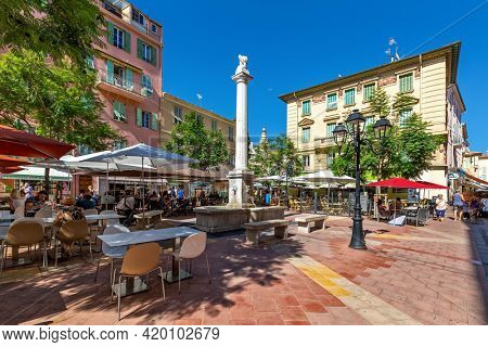 MENTON, FRANCE - AUGUST 21, 2020: People sitting in outdoor restaurants on small town square among beautiful buildings in Menton - famous resort and popular travel destination on French Riviera.
