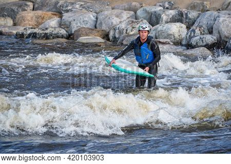 Fort Collins, CO, USA - May 7, 2021: Male surfer wearing a wetsuit and helmet is getting ready to surf a river wave in the Poudre River Whitewater Park.