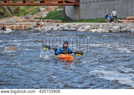 Fort Collins, CO, USA - May 7, 2021: Young male kayaker wearing a drysuit is paddling his kayak in the Poudre River Whitewater Park, spring scenery with high river flow.