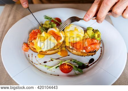 Eggs Benedict. The Poached Egg Is Cut With A Knife. Breakfast Plate. Eggs Benedicts On Toast, Close-