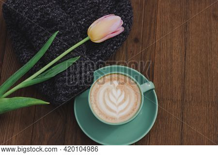 Knitted Hat, Tulip And Cappuccino In A Green Mug. Cozy Atmosphere. Wooden Background. Layout