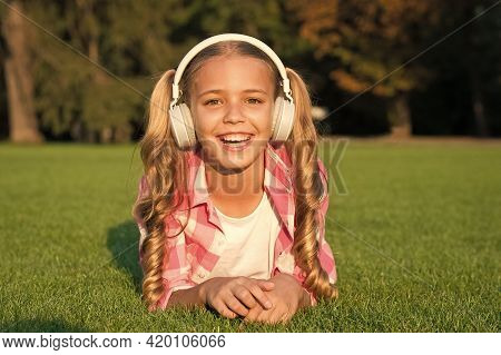 Listening To Music. Back To School. Kid Study In Park. Relax On Green Grass In Headphones. Small Gir