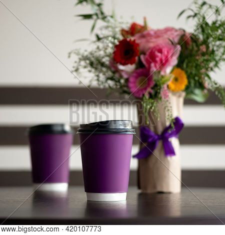 Coffee Drink In Paper Cups On Table. Purple Disposable Cardboard Cups And Bouquet Of Roses On Blurre
