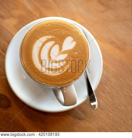 Top View Of Creamy Cappuccino. Cup Of Coffee Drink With Heart Drawn On Foam. White Ceramic Cup With