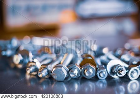 Metal Chrome Bolts And Nuts In A Chaotic Order Industrial Background